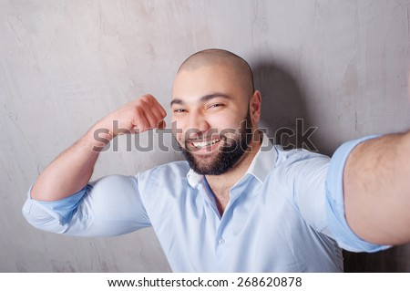 Sport and selfie! Handsome young latino man in shirt holding camera and making selfie and showing his strong muscles while standing against grey wall.