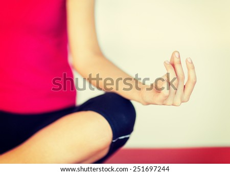 sport and yoga concept - girl sitting in lotus position and meditating - stock photo