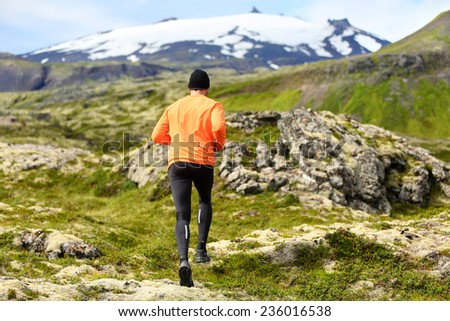 Sport athlete - exercising trail runner running. Active male fitness model training and jogging outdoors in beautiful mountain nature landscape by Snaefellsjokull, Snaefellsnes, Iceland. - stock photo