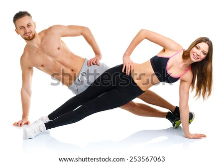 Sport attractive couple - man and woman doing fitness exercises on the white background
