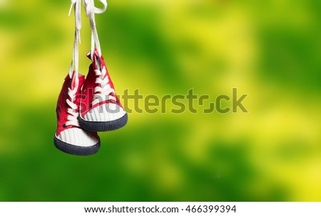 Sport baby shoes hanging on the rope
