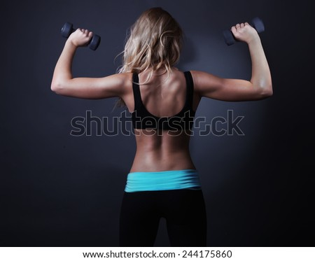Sport back of athletic woman with dumbbells. - stock photo