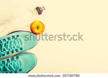 sport background: blue running shoes  and apple with objects isolated on white background - stock photo
