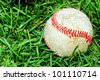 Sport background: old ans used baseball in the green grass field - stock photo