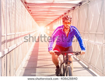 Sport bike man riding inside urban tunnel with light - Healthy cyclist on professional bicycle training day inside metal bridge - Concept of active green lifestyle and outdoor hobby - Sun halo filter - stock photo