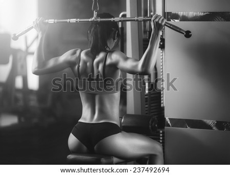 Sport. Black and white photo fitness woman from behind. Brunette sexy fitness girl in sport wear with perfect body in the gym posing before training set. Attractive fitness woman, trained female body - stock photo