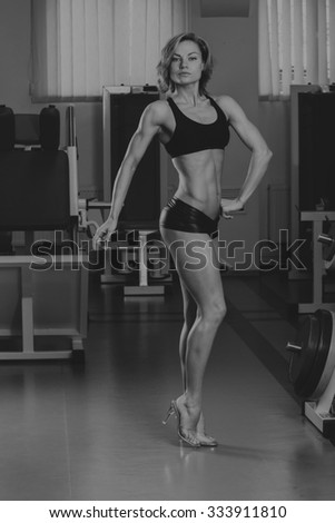 Sport blonde. Beautiful strong girl. Bodyfitness, women's fitness. Woman doing exercises at the gym. Beauty, health, and sports.Bodybuilder young adult sexy girl