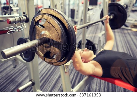 sport, bodybuilding, lifestyle and people concept - close up of man flexing biceps with barbell in gym