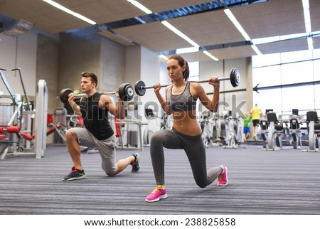 sport, bodybuilding, lifestyle and people concept - young man and woman with barbell flexing muscles and making shoulder press lunge in gym - stock photo