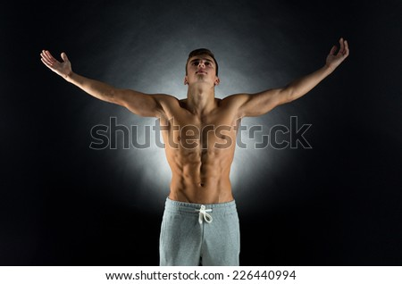sport, bodybuilding, strength and people concept - young man standing with raised hands over black background - stock photo