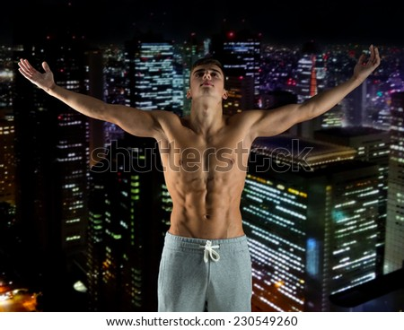 sport, bodybuilding, strength and people concept - young man standing with raised hands over night city background - stock photo