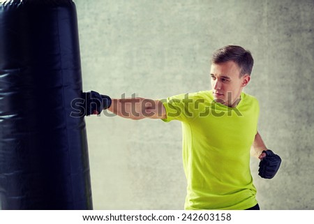 sport, box and people concept - young man in gloves boxing with punching bag in gym - stock photo