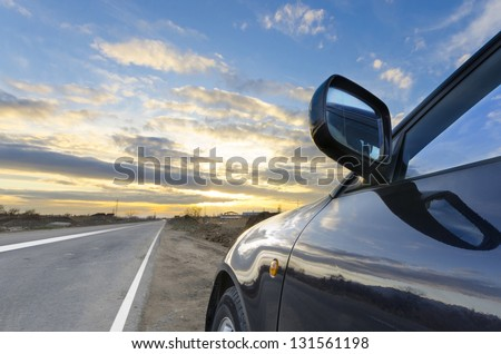 Sport car ride on road in sunset weather - stock photo
