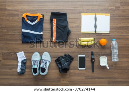 Sport clothes and accessories on a wooden background, View from above - stock photo