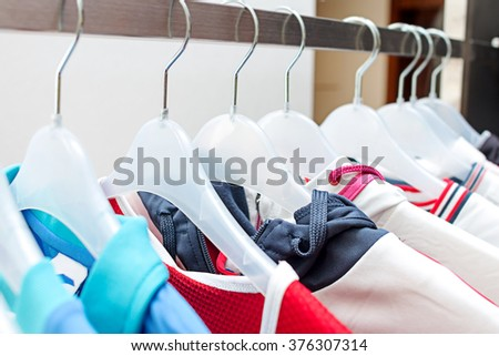 Sport clothes on hangers. Sport clothes on clothes rail in clothing store on hangers. Man's sport clothes hanging in wardrobe. Clothes hanging on the rack in the store. Rod with hangers. - stock photo