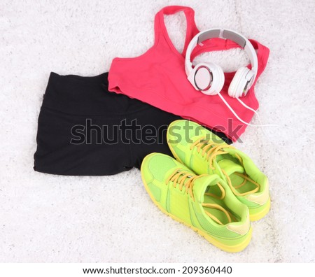 Sport clothes, shoes and headphones on white carpet background.  - stock photo