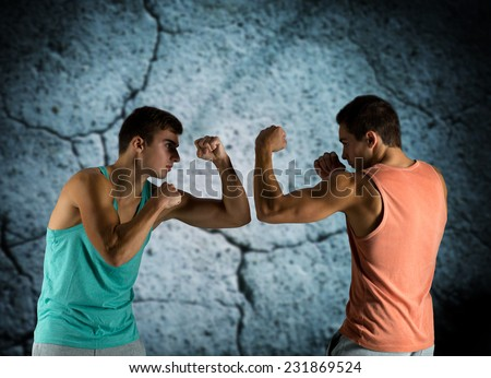 sport, competition, strength and people concept - young men fighting hand-to-hand over concrete wall background - stock photo