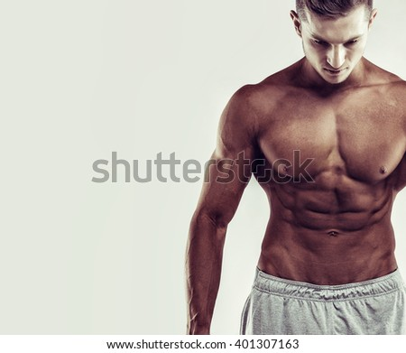 Sport concept. Close up image of muscular caucasian male in sports clothing over grey background.