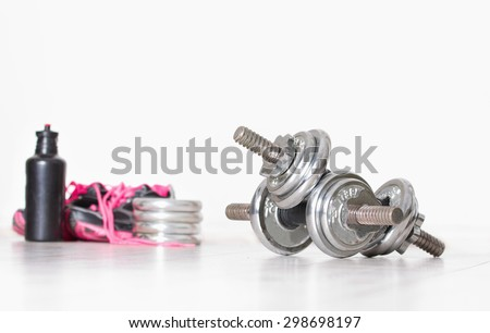 Sport concept. Close up of two steel dumbbells and pink sneakers and bottle of water in background