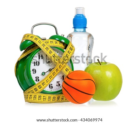 Sport concept - green alarm clock with ball, apple, measuring tape and water,  isolated on white background