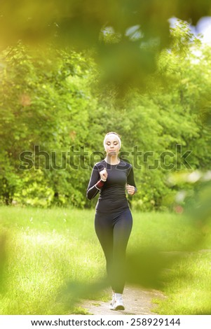 Sport Concept: Positive Caucasian Fit Woman Having Her Regular Jogging Exercises in The Forest Outdoors. Vertical Image Composition - stock photo