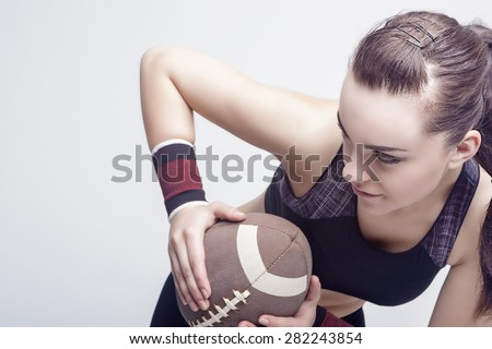 Sport Concepts: Professioanl Female Soccer Player With Ball for American Football. Horizontal Image Orientation - stock photo