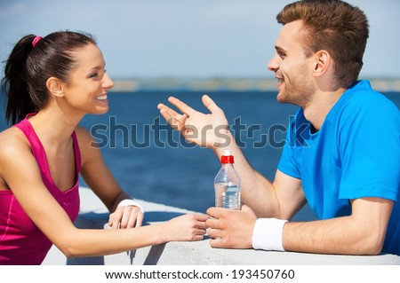 Sport connecting people. Side view of beautiful young couple in sports clothing standing face to face and talking - stock photo