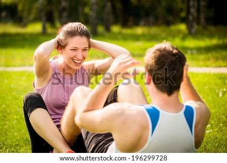 Sport couple making sit-ups together in nature on green grass - stock photo