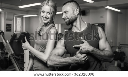 Sport couple on training in the gym. Healthy life. Help and support when performing exercises. Photos for sporting magazines and websites. - stock photo