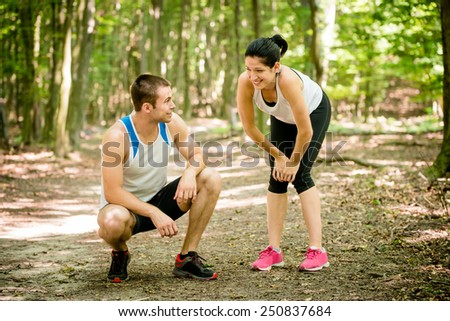 Sport couple relaxing after jogging in nature (foot bridge in forest) - stock photo