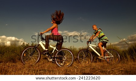 Sport couple riding bikes in field - stock photo