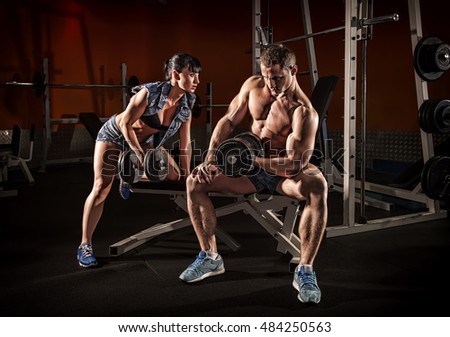 Sport couple showing muscles and workout in the gym.