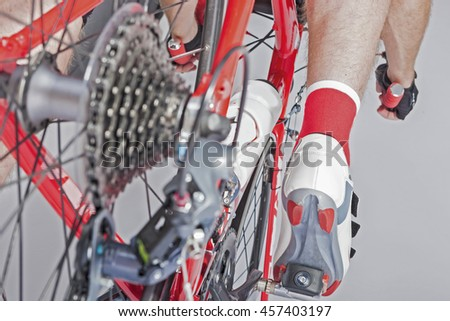 Sport Cycling Concepts. Back View of the Athlete Leg Inline with Rear Derailleur and Cassette Sprockets. Back View. Horizontal Image