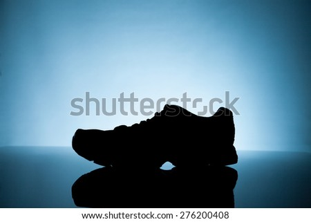 Sport equipment. silhouette of Sneakers on a blue background - stock photo