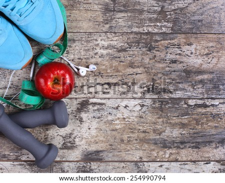 Sport equipment. Sneakers, dumbbells, measuring tape and earphones on wooden background  - stock photo