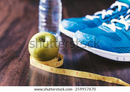 Sport equipment. Sneakers, water, apple and meter on wooden background - stock photo