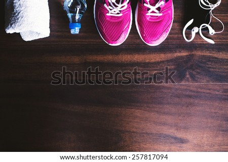Sport equipment. Sneakers, water, towel, earphones and phone on wooden background - stock photo