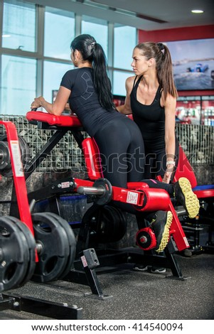 Sport exercises for legs. Two women athletes engaged in the gym and lift the weight of your feet. Coach helps females engaged client. - stock photo