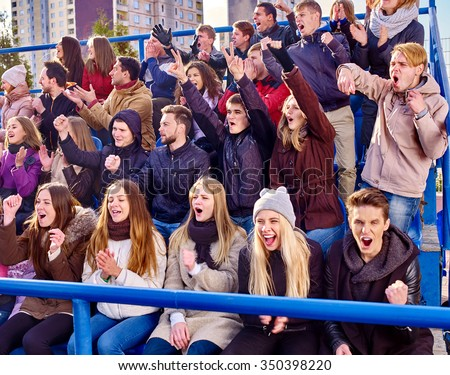 Sport fans clapping and crying on tribunes. Group adult people. - stock photo