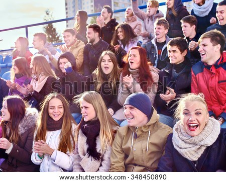 Sport fans clapping and singing on tribunes. Group happy young people. - stock photo