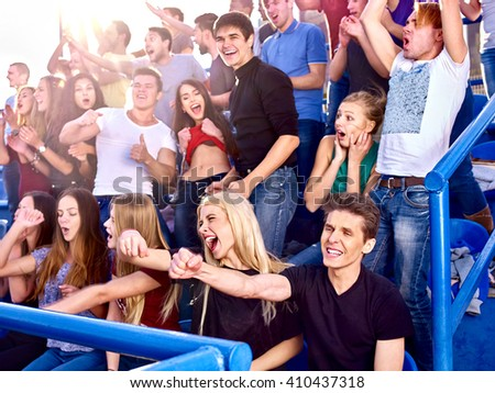 Sport fans hands up and singing  on tribunes. - stock photo