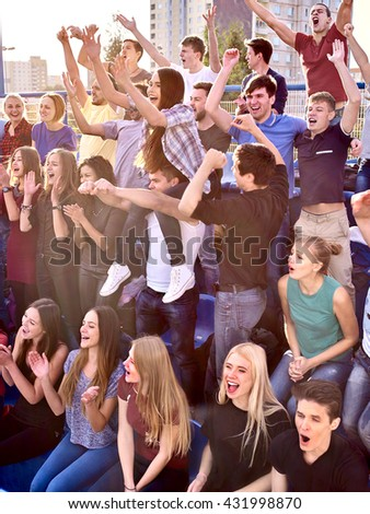 Sport fans hands up and singing on tribunes. Group people in sport. - stock photo
