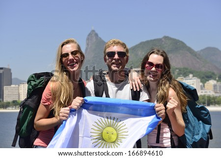 Sport fans holding Argentina Flag in Rio de Janeiro with Christ the Redeemer in background. - stock photo