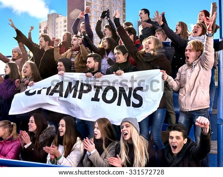 Sport fans holding champion banner  and singing on tribunes. Group people. - stock photo