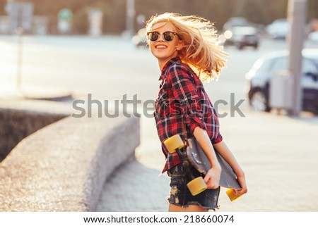 Sport fashion girl posing in summer with skateboard - stock photo