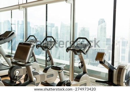 sport, fitness and health care concept - exercise bikes in city gym - stock photo