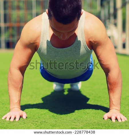 Sport, fitness and workout concept - Sportsman doing push-ups exercise outdoors - stock photo