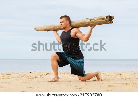Sport, fitness. Bodybuilder with a big wood on the beach - stock photo