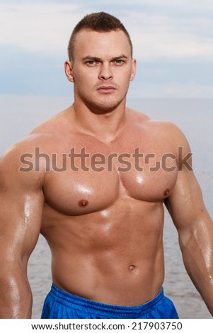 Sport, fitness. Bodybuilder with sexy body on the beach