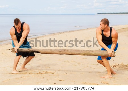 Sport, fitness. Bodybuilders during workout on the beach - stock photo